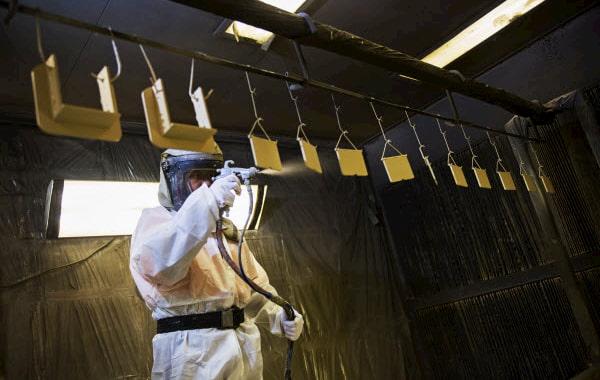 Man in full gear spraying paint inside the shop