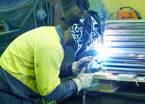 Man wearing full safety welding mask while welding a steel