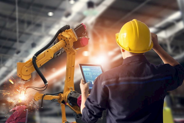Engineer using tablet check and control automation robot arms