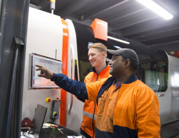 Two men worker operating equipment through a computer