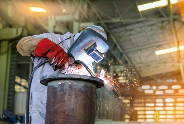 Man welding steel pipe by mig in factory