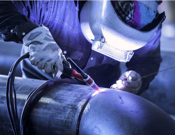 Worker welding metal piping using tig welder