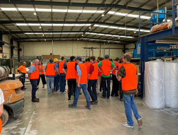 A group of people wearing orange vest at the warehouse